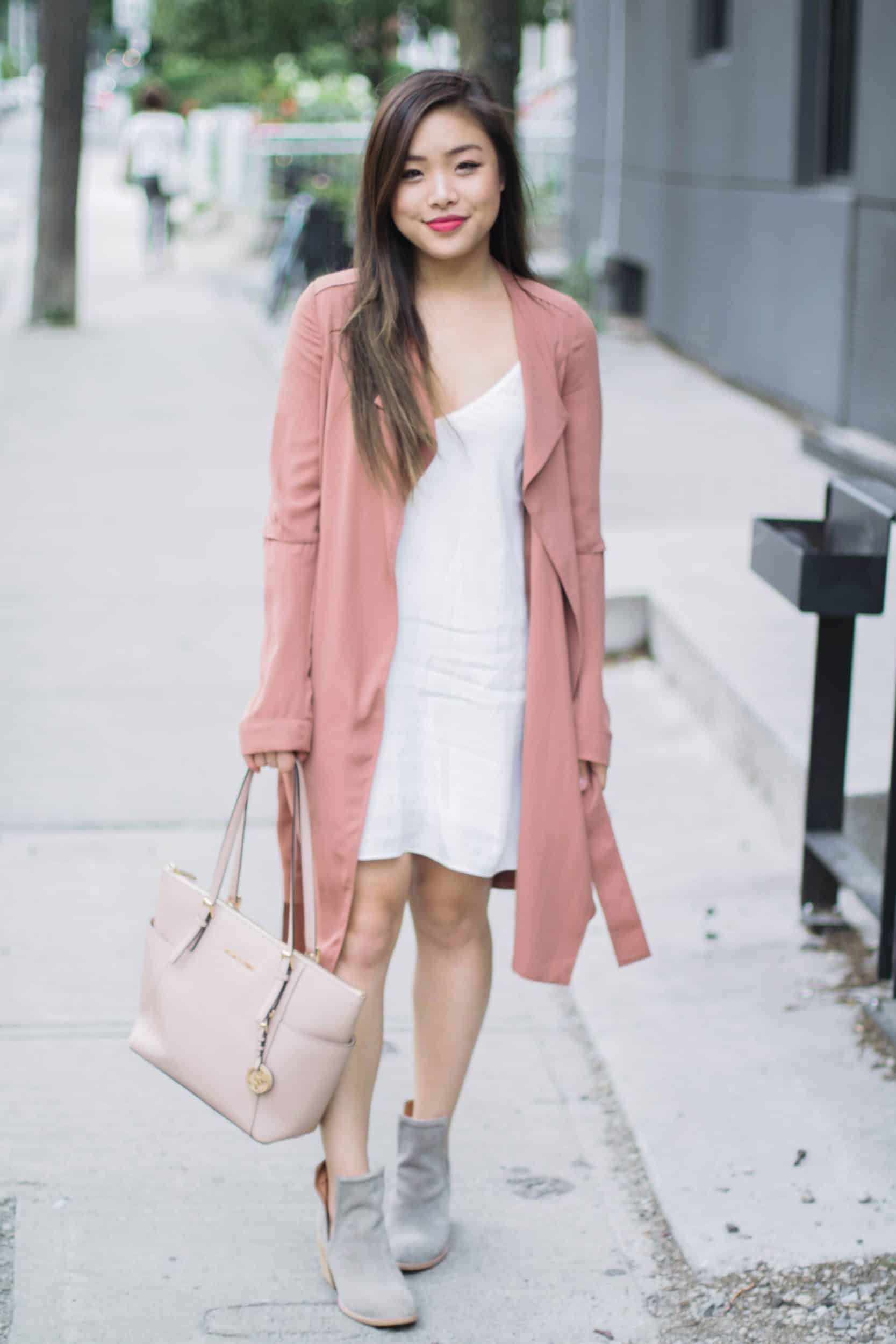Summer outfit featuring Aritzia white slip dress, pink trench coat, Jeffrey Campbell grey suede booties, and nude Michael Kors bag
