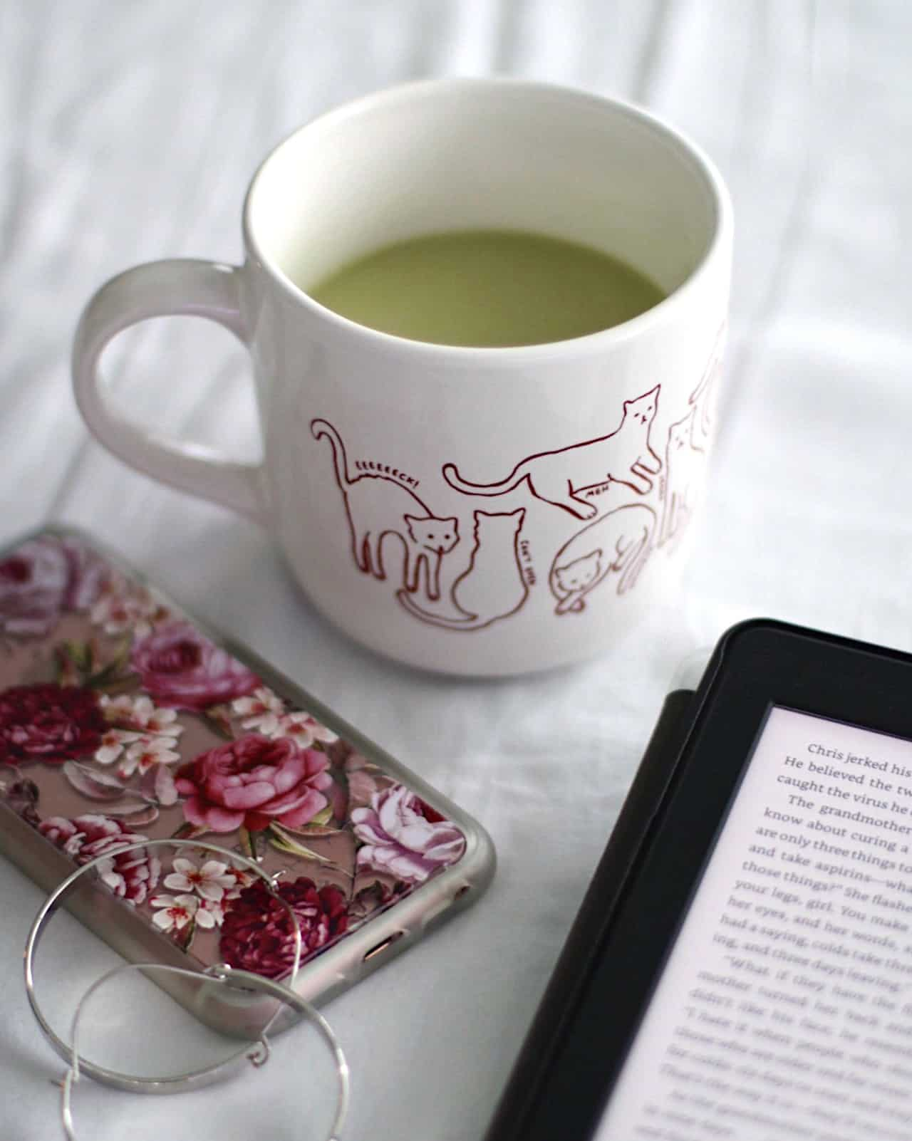 Floral phone case, matcha latte, and Kindle flat lay