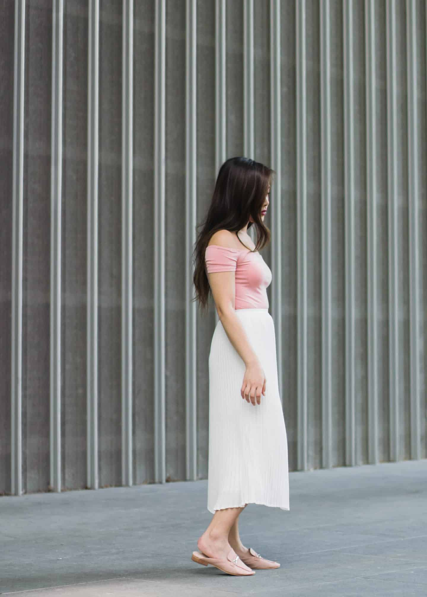 Pleated white midi skirt with pink off shoulder bodysuit and pink flat mules