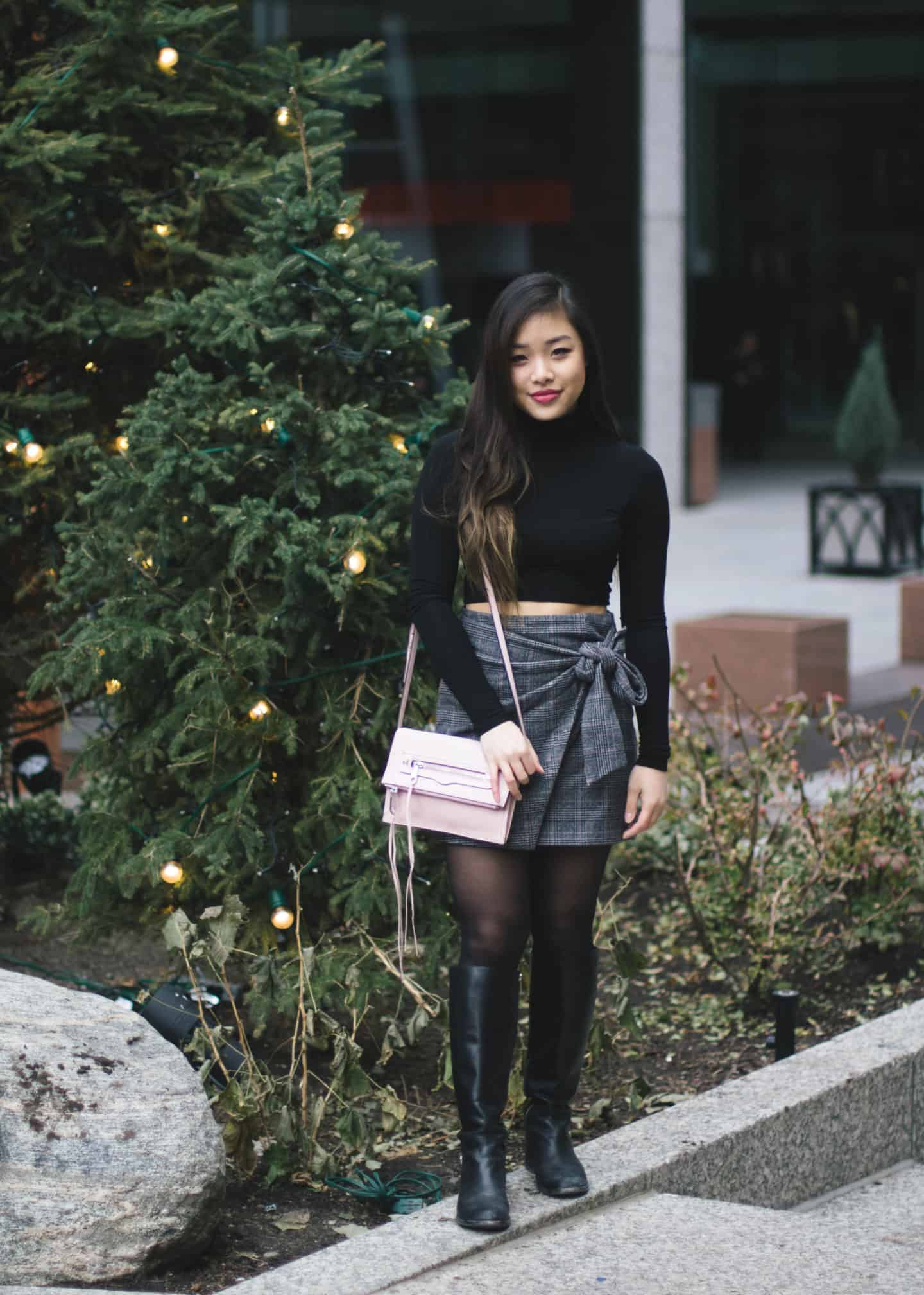 Holiday outfit idea featuring black turtleneck, plaid skirt, and tall leather boots