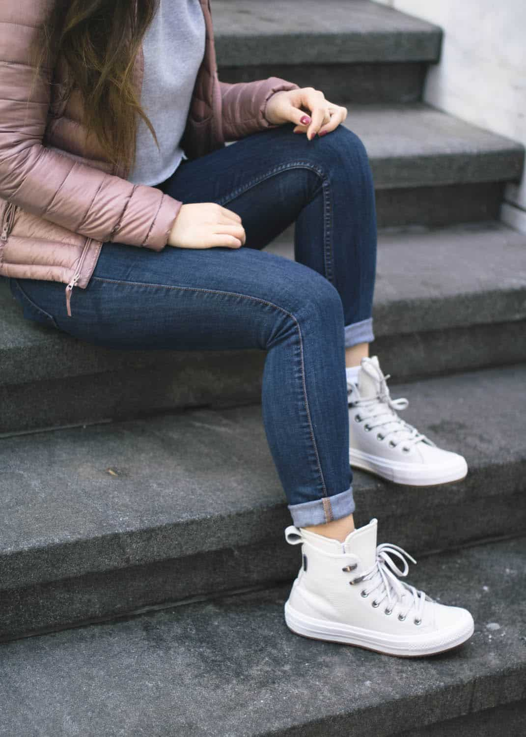Winter outfit idea featuring Aritzia pink puffer jacket, cropped grey hoodie, Guess denim, and Converse Winter Boots