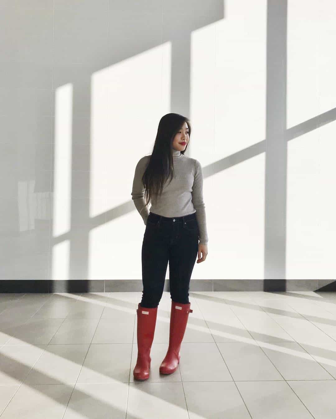 Winter outfit idea featuring a beige wool turtleneck, dark wash high waisted jeans, and red Hunter boots