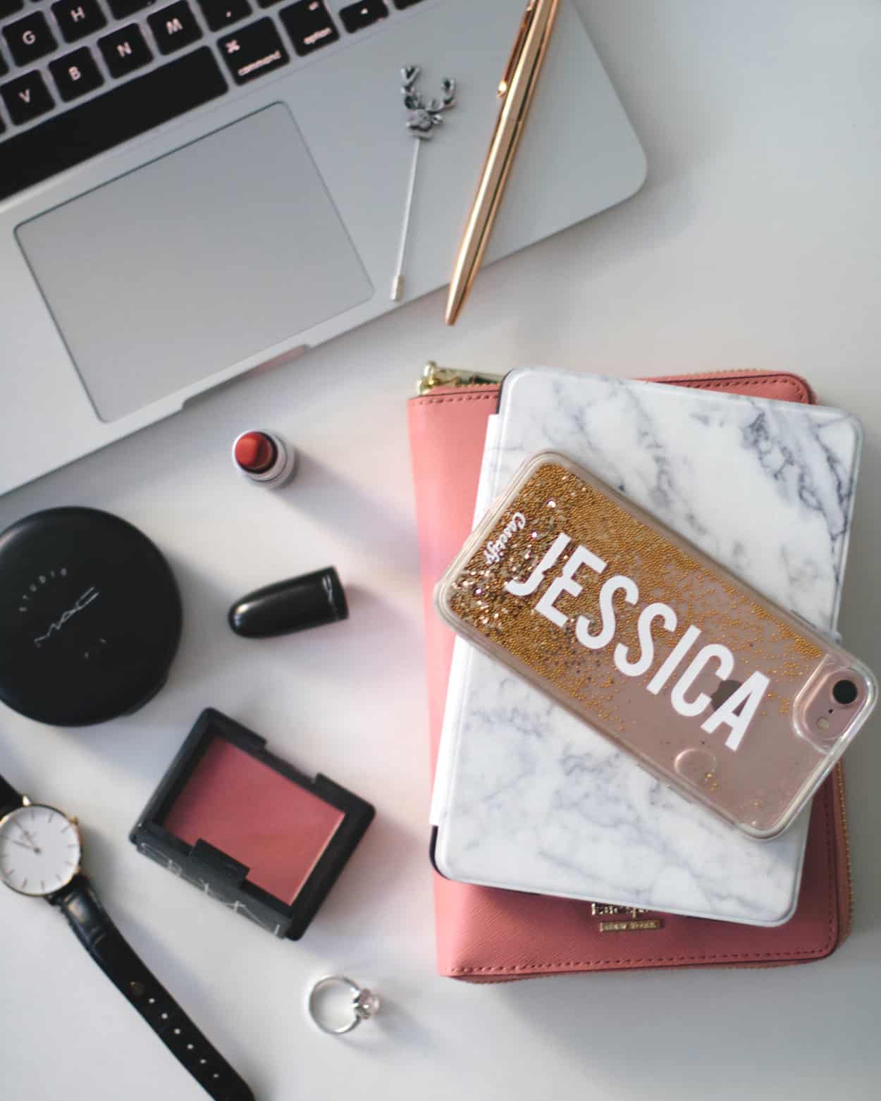 Work flat lay with laptop, phone, Kindle, planner, and beauty products