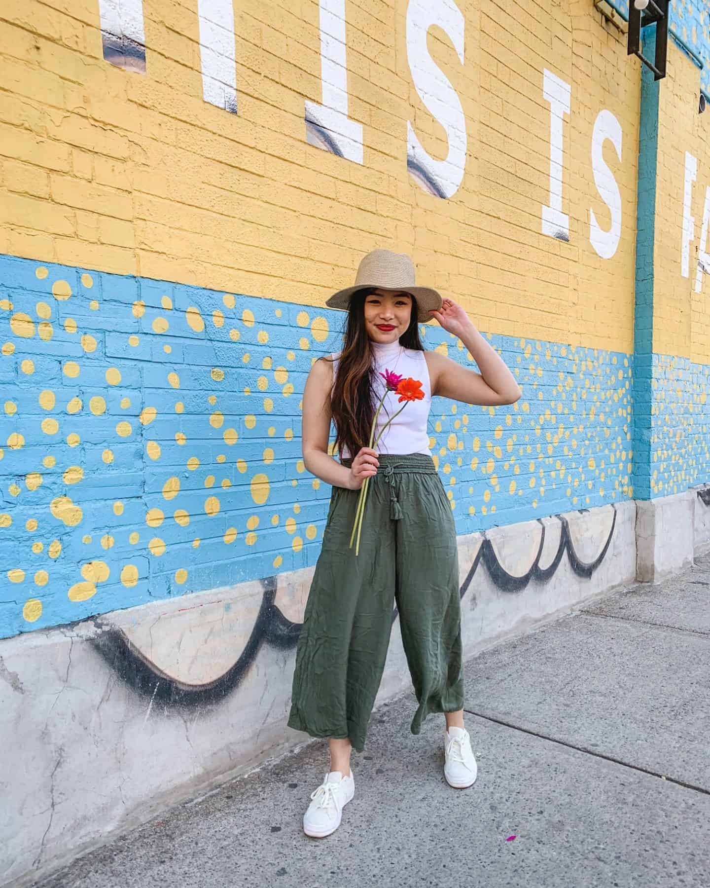 This is Paradise mural on Queen Street West in Toronto - wearing Aritzia straw hat, white sleeveless mock turtleneck, military green wide leg pants, Converse One Star sneakers