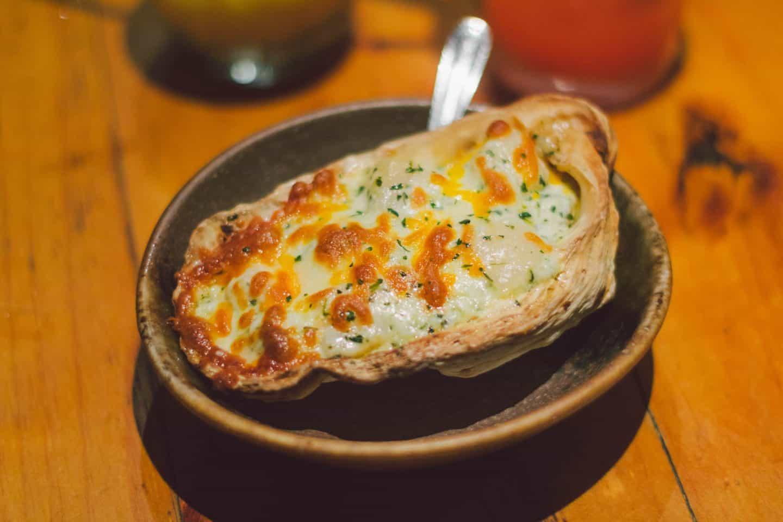 The Kakimayo dish at Kinka Izakaya, a baked oyster topped with spinach, mushrooms, garlic mayo, and cheese