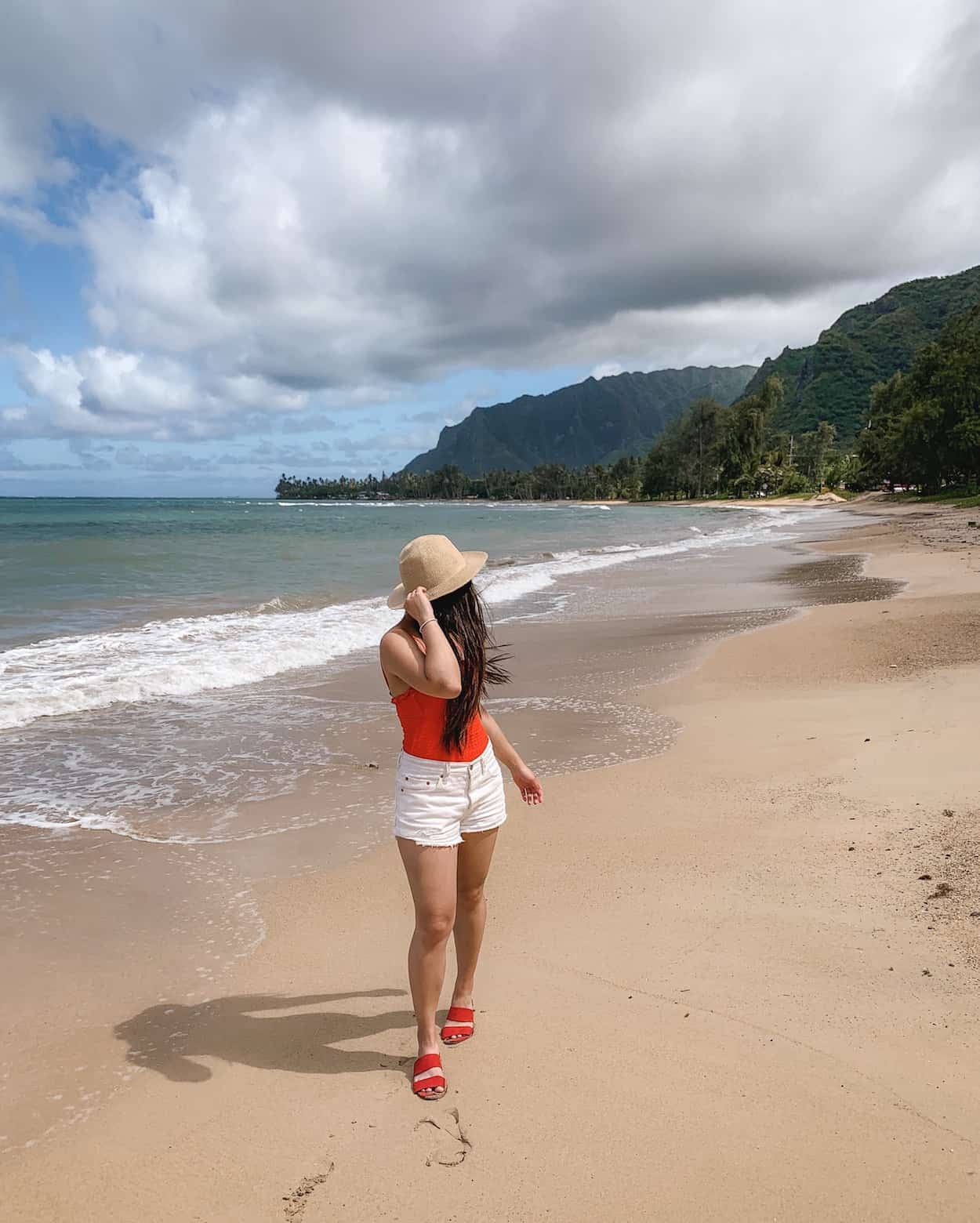 Hawaii vacation outfit featuring straw hat, red one piece swimsuit, white denim shorts, and red slide sandals