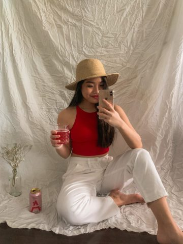 Drinking Ace Hill vodka soda while wearing Aritzia straw hat, American Apparel red crop top, and Levi's white balloon pants